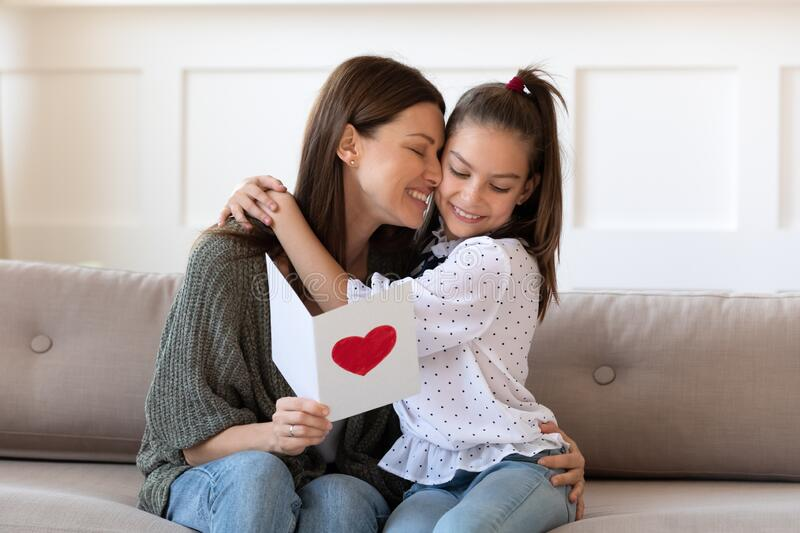 Happy mum hug little daughter thank for birthday surprise. Happy young mom sit on couch hug cuddle little daughter thanking for beautiful postcard present stock image