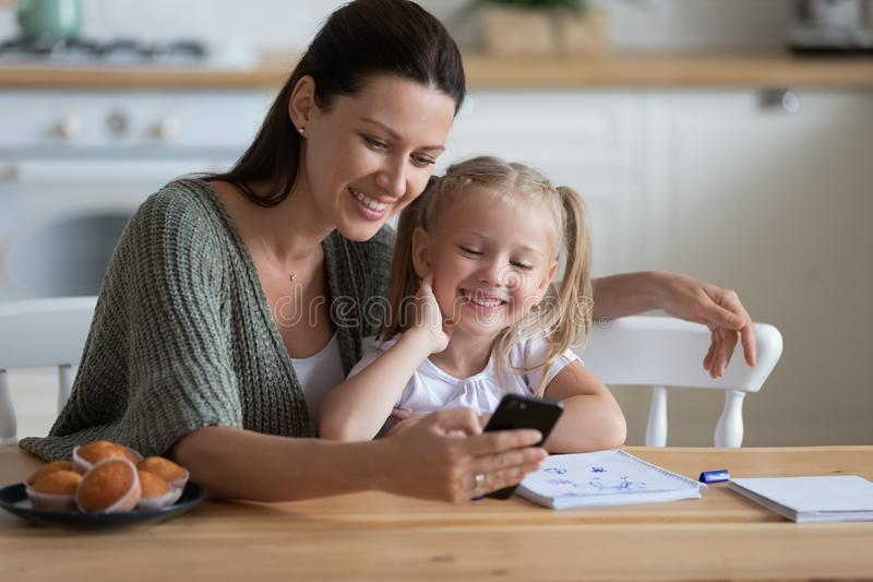 Happy mum and kid daughter using smartphone at kitchen table royalty free stock images
