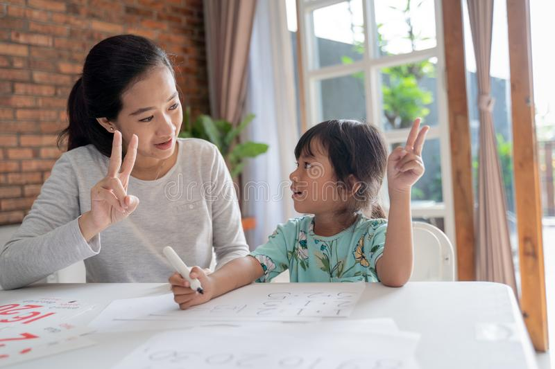 Mum and kid learning maths together at home stock images