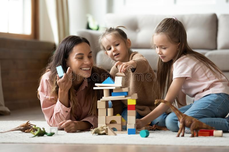 Happy mum with kids daughters playing toys on floor. Happy young mum babysitter helping playing game with little kids daughters on floor, female nanny mother and royalty free stock images