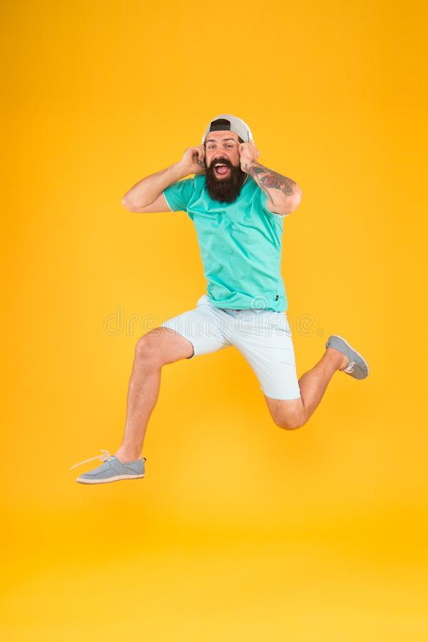 Happy music. Happy hipster jumping on music on yellow background. Bearded man enjoying song playing in headphones with stock image