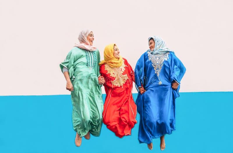 Happy Muslim girls jumping together outdoor - Arabian women having fun in the college stock photo