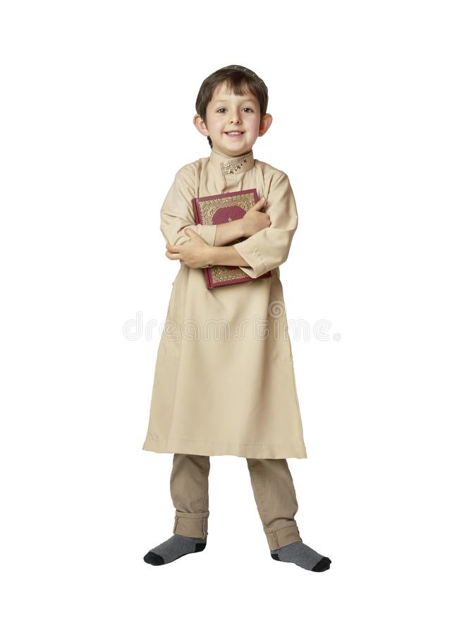 Happy muslim kid holding holy Koran on white background. Happy muslim kid holding holy Koran stock photo