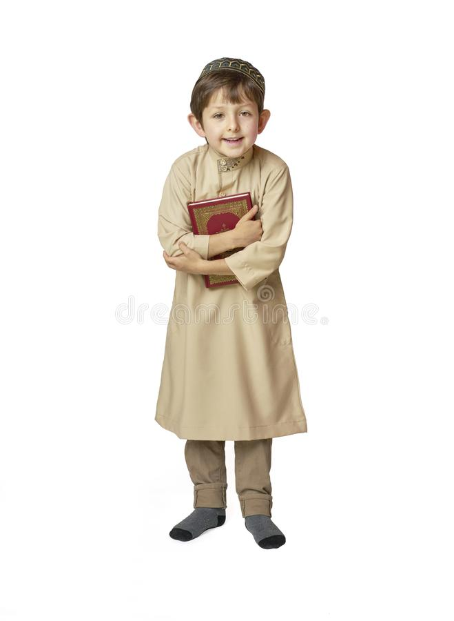 Happy muslim kid holding holy Quran on white background. Happy muslim kid holding holy Koran royalty free stock photos