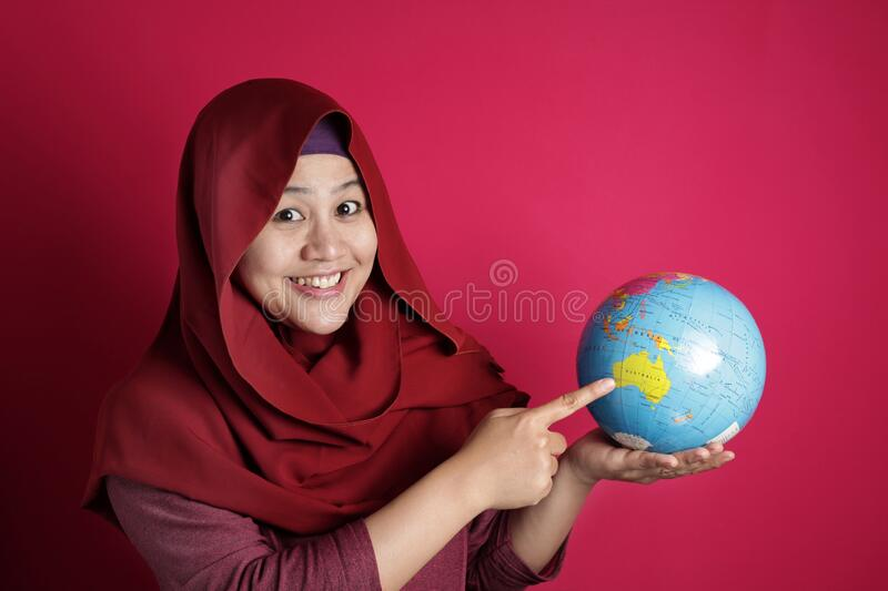 Happy muslim woman pointing earth globe map on her hand, geography study, global business or vacation plan concept. Happy muslim woman wearing red hijab smiling royalty free stock images