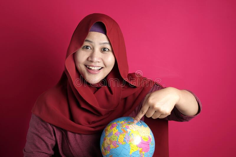 Happy muslim woman pointing earth globe map on her hand, geography study, global business or vacation plan concept. Happy muslim woman wearing red hijab smiling stock photos