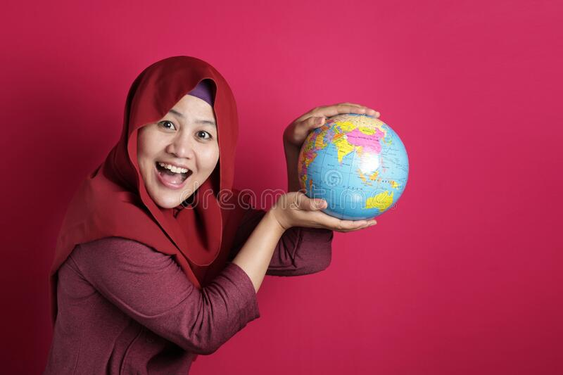 Happy muslim woman presenting earth globe map on her hand, geography study, global business or vacation plan concept. Happy muslim woman wearing red hijab royalty free stock images
