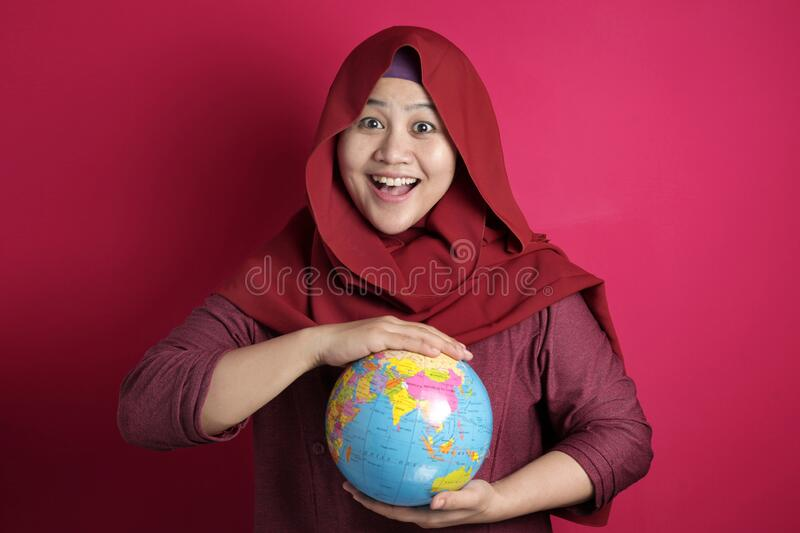 Happy muslim woman presenting earth globe map on her hand, geography study, global business or vacation plan concept. Happy muslim woman wearing red hijab royalty free stock photography