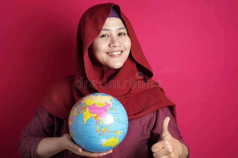 Happy muslim woman presenting earth globe map on her hand, geography study, global business or vacation plan concept. Happy muslim woman wearing red hijab stock images