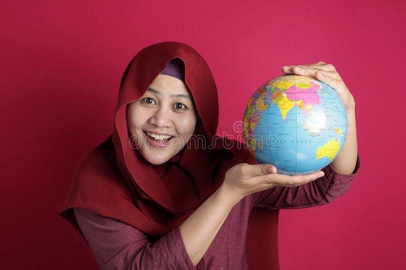 Happy muslim woman presenting earth globe map on her hand, geography study, global business or vacation plan concept. Happy muslim woman wearing red hijab royalty free stock photos