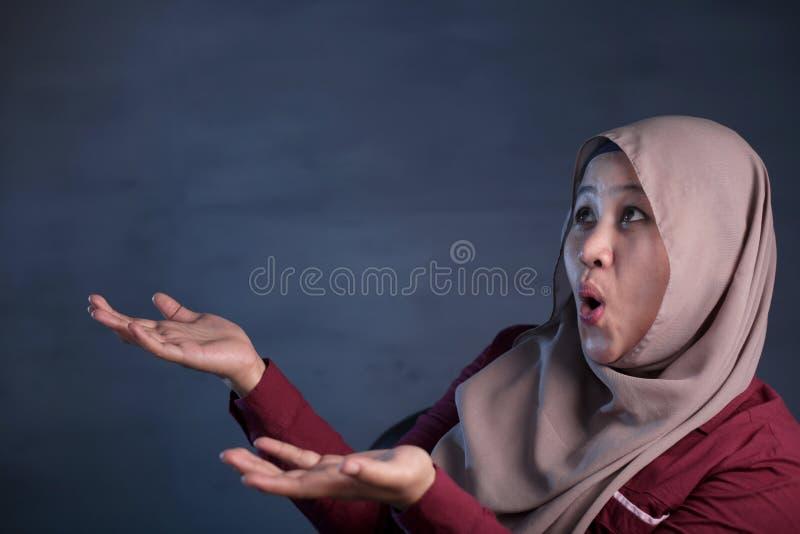 Happy Muslim Woman Shows Winning Gesture Greeting Something. Portrait of happy muslim woman celebrating victory, winning gesture smiling and greeting something royalty free stock photos