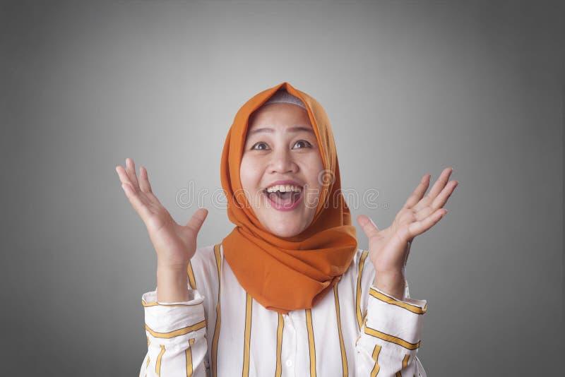 Happy Muslim Woman Shows Winning Gesture Greeting Something. Portrait of happy muslim woman celebrating victory, winning gesture smiling and greeting something royalty free stock image