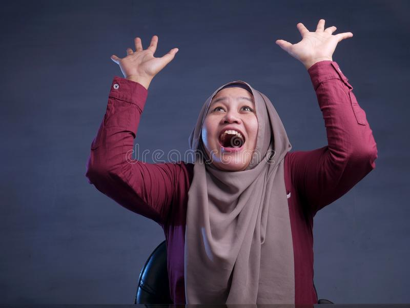Happy Muslim Woman Shows Winning Gesture Greeting Something. Portrait of happy muslim woman celebrating victory, winning gesture smiling and greeting something stock images
