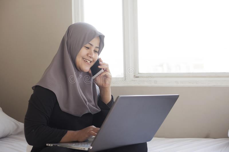 Happy Muslim Woman Working with Laptop and Smart Phone in Her Bedroom royalty free stock photos