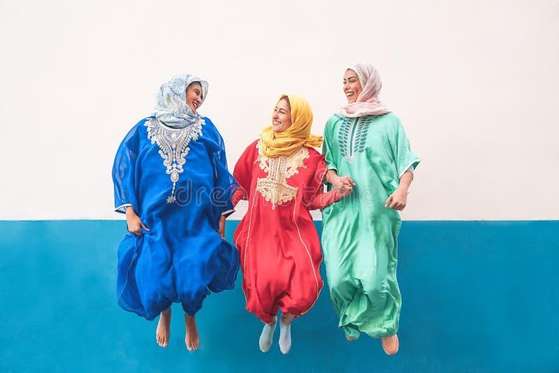 Happy muslim women jumping together outdoor - Arabian teen girls having fun in the city stock photos