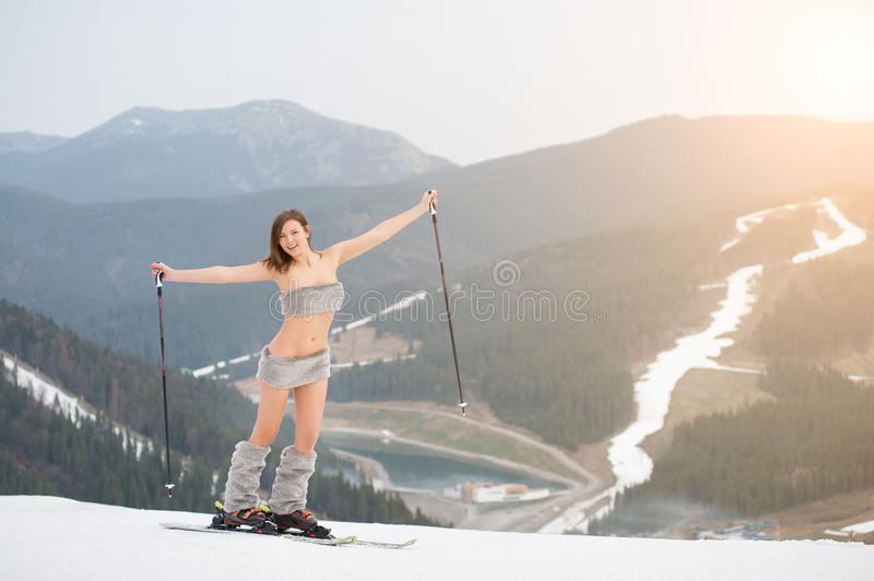 Happy naked female skier standing on the snowy slope of the mountain, rising hands up, wearing ski equipment. Looking to the camera. Ski resort, snowy slopes stock photos