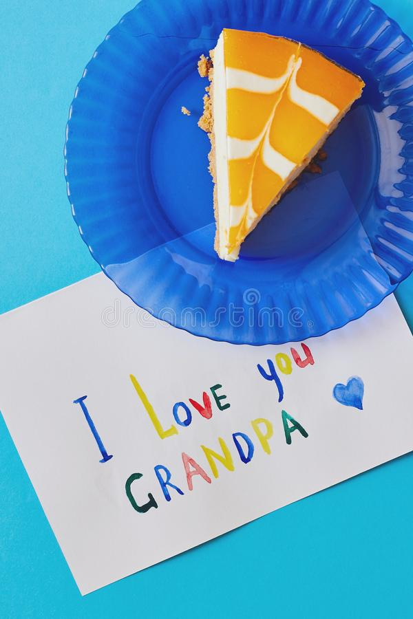 Happy National Grandparents day. Colored greeting card made by children and piece of cake on blue plate as gift stock photography