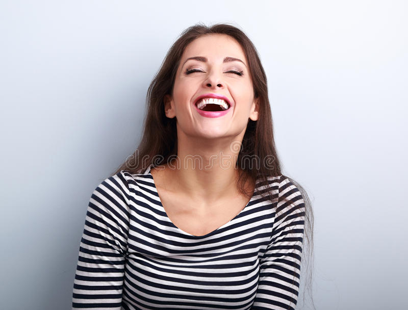 Happy natural laughing young casual woman with wide open mouth a. Nd closed eyes on blue background royalty free stock images