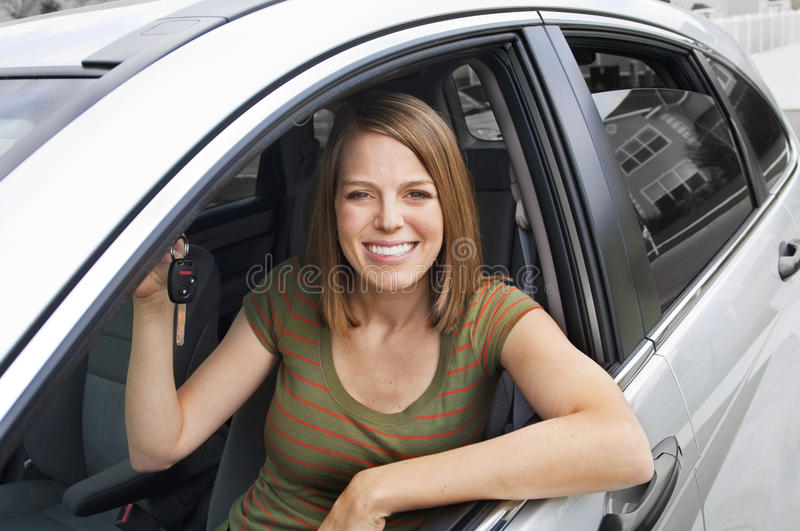 Happy New Car Owner. A beautiful Woman ready to drive her new car purchase stock photography