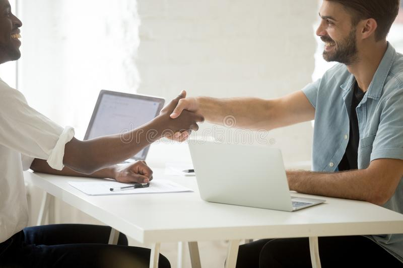 Happy new multiracial diverse partners shaking hands starting bu. Siness together or closing contract deal, smiling african and caucasian businessmen celebrating royalty free stock images