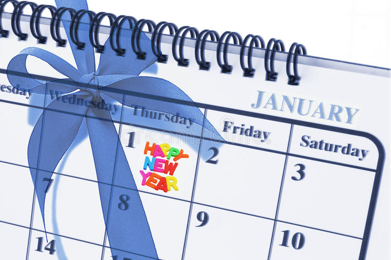 Happy New Year. Composite images of calendar page showing January 1 Happy New Year and blue bow ribbon on gift box royalty free stock images