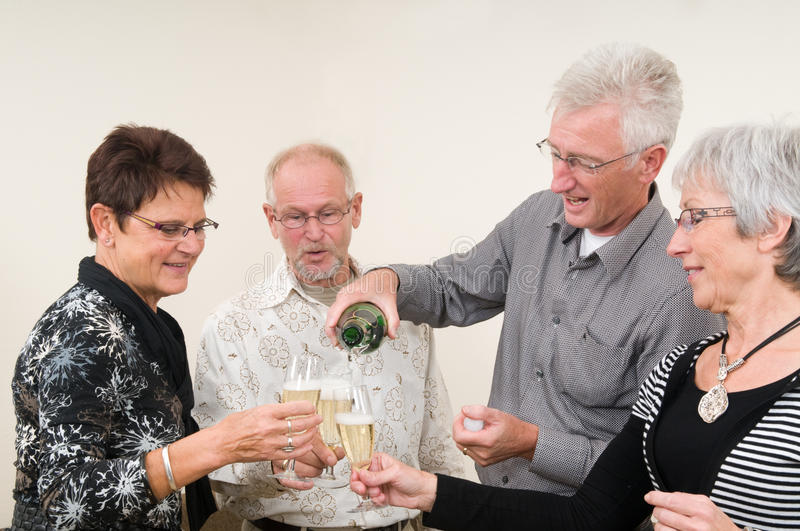 Happy New Year. Two senior couples toasting on a Happy New Year stock images