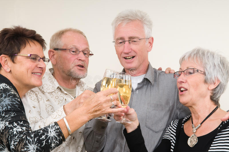 Happy New Year. Two senior couples toasting on a Happy New Year stock image