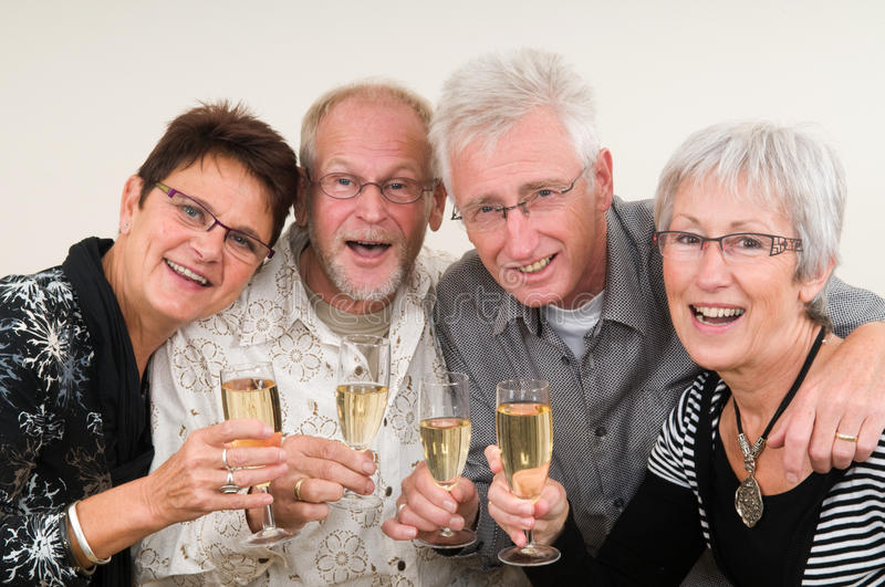 Happy New Year. Two senior couples toasting on a Happy New Year stock photo
