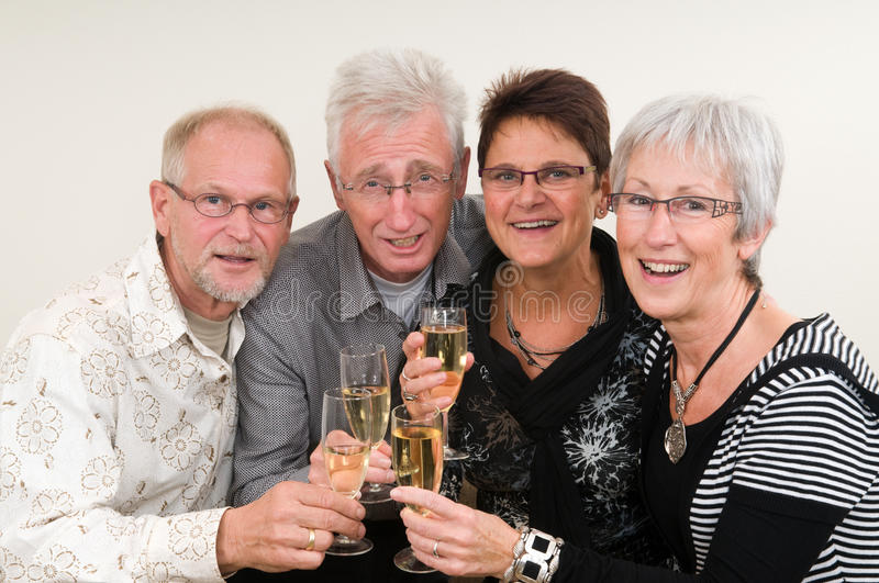 Happy New Year. Two senior couples toasting on a Happy New Year stock photography