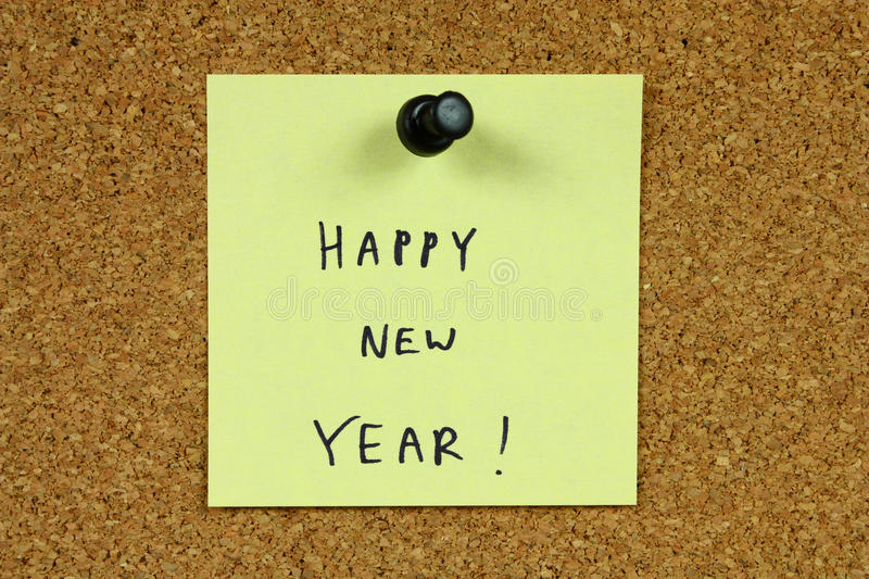 Happy New Year. Yellow small sticky note on an office cork bulletin board. Happy New Year stock photos