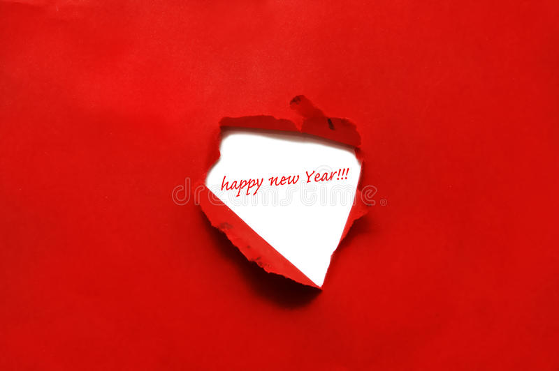 Happy new year. Written on a hole on a red cardboard background stock images