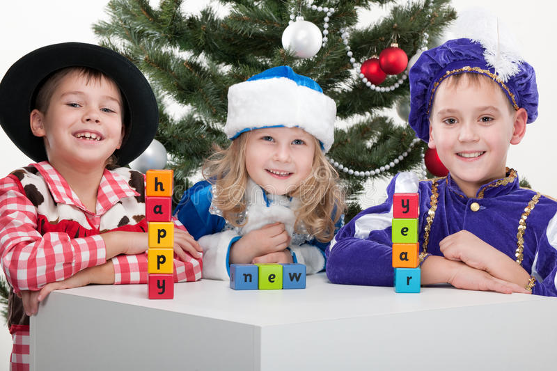 Happy new year!. Three children dressed in carnival suits are greeting with sigh happy new year made with blocks at the decorated christmas tree; isolated on the royalty free stock photo