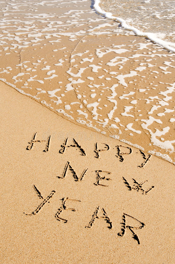 Happy new year. Sentence happy new year written in the sand of a beach stock photography