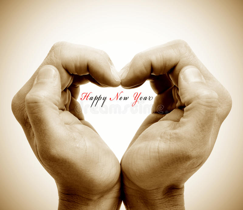 Happy new year. Hands forming a heart and the sentence happy new year royalty free stock photography