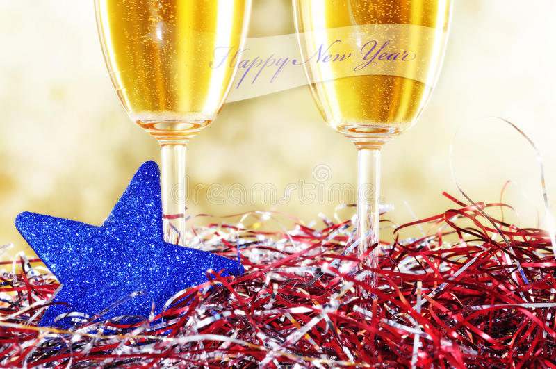 Happy new year. A pair of glasses of champagne with the sentence happy new year and some christmas ornaments royalty free stock photo
