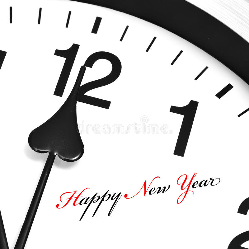 Happy new year. Written in a clock with its hands ticking midnight royalty free stock photo