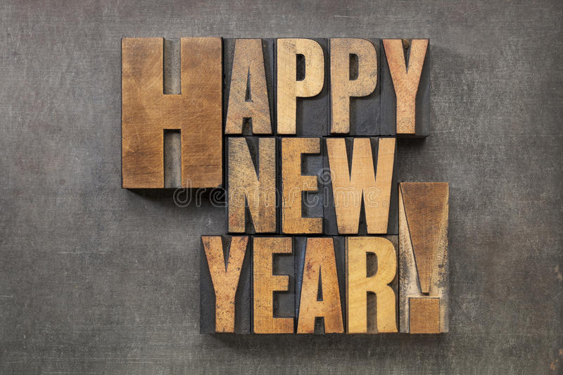 Happy New Year!. Text in vintage letterpress wood type blocks on a grunge metal background stock photo