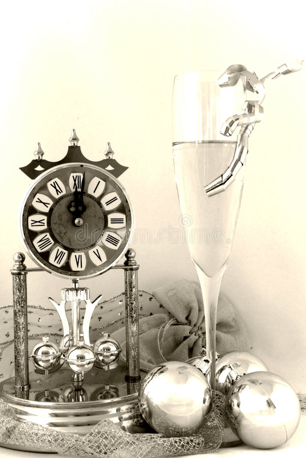Happy new year!. The clock strikes 12 and the new year begin. Clock, champagne, candle, golden balls and ribbon in white background and old light stock photos