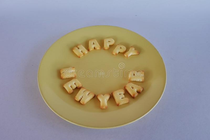 Happy new year alphabet crackers on yellow dish. Happy new year stock photo
