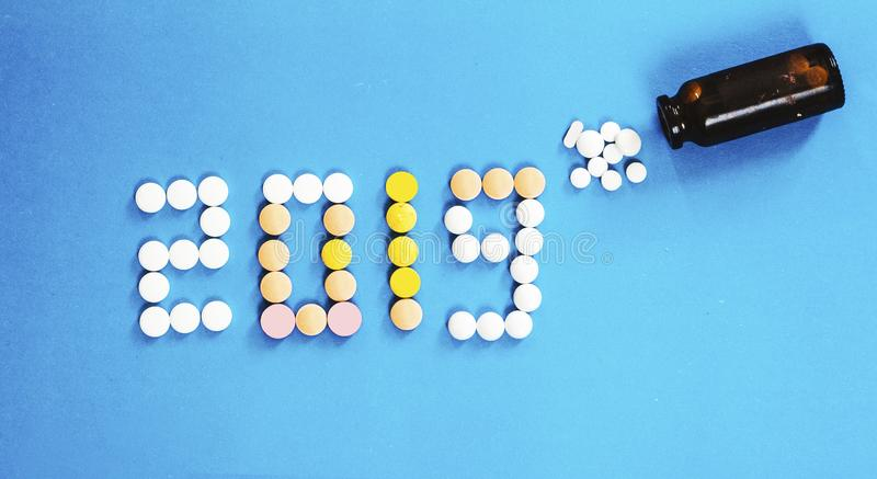 Happy New Year banner for medical theme. Number 2019 made by colored pills/tablets spilling out of brown glass bottle on blue back royalty free stock photo