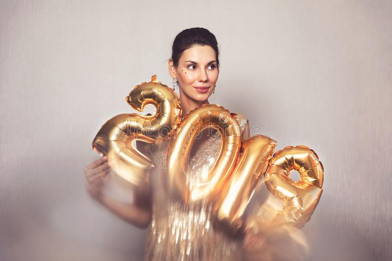 Happy New Year. Beautiful Woman with Balloons Celebrating new year`s Eve Party. Smiling Girl in Bright Shiny Dress with royalty free stock photography