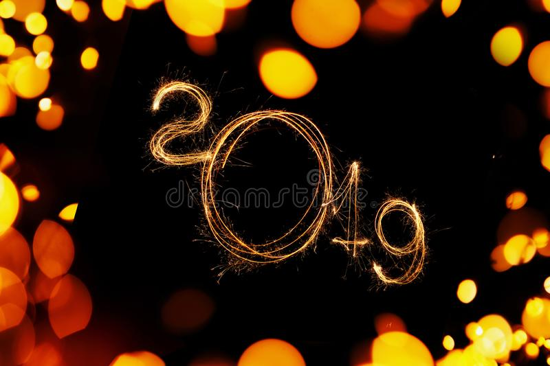 Happy New Year 2019 on a black background with yellow lights bokeh. 2019 sparkler. royalty free stock image