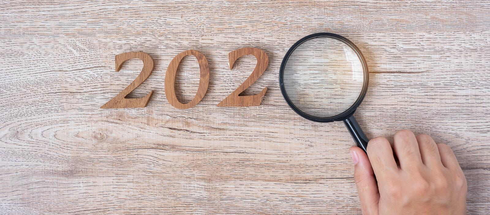2020 Happy New year with Businessman holding glass magnifying and wooden number on table. New Start, Vision, Resolution, Strategy. Goals, Mission and Search royalty free stock photo