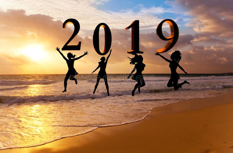 Happy new year card 2019. Silhouette young woman jumping on tropical beach over the sea and 2019 number with sunset background royalty free stock images