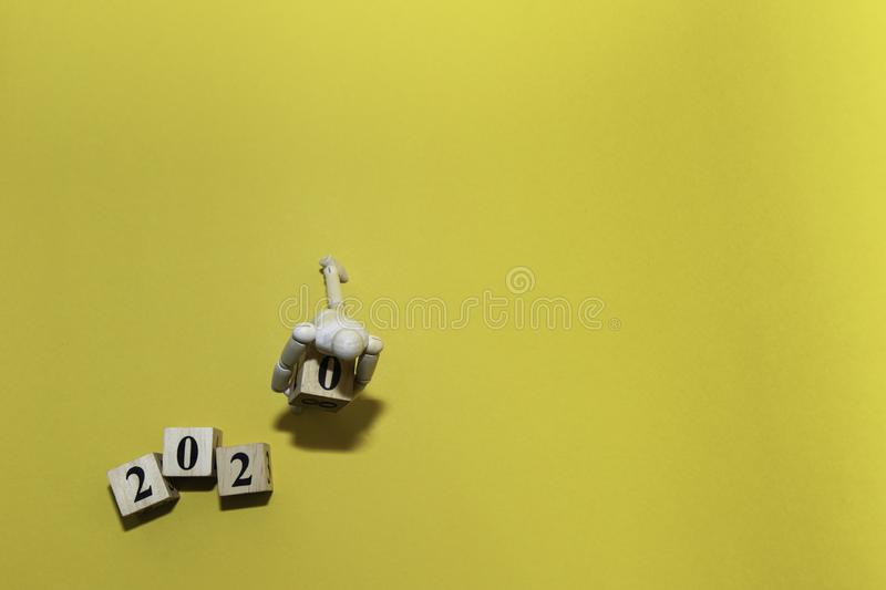 Happy New year 2020 celebration concept with top view Wooden human doll is carrying wood cube of zero number on yellow stock image