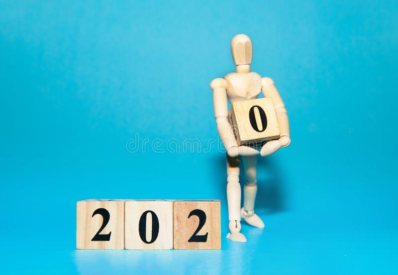 Happy New year 2020 celebration concept with Wooden human ​​doll is carrying wood cube stock photos