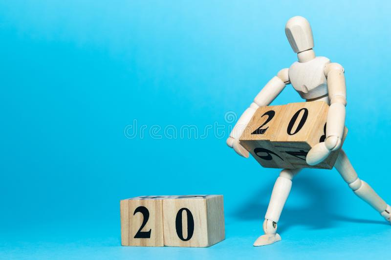 Happy New year 2020 celebration concept with Wooden human doll is carrying wood cube of twenty number on blue background stock images