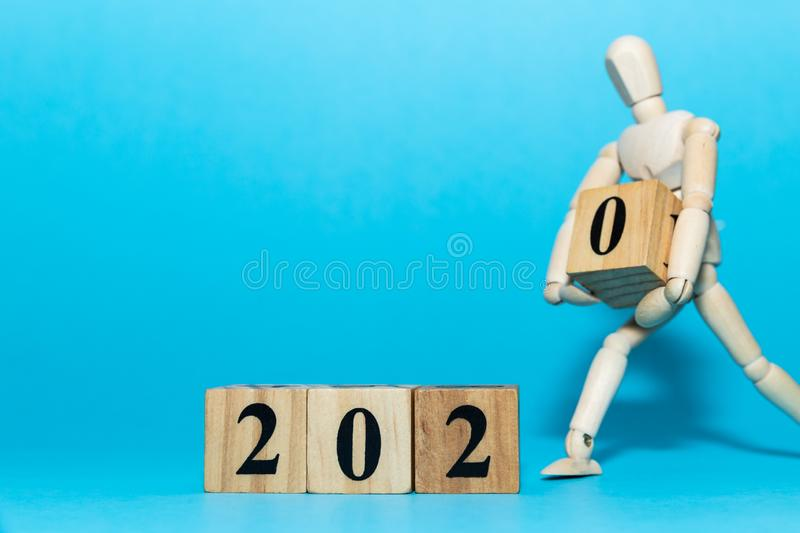 Happy New year 2020 celebration concept with Wooden human doll is carrying wood cube of zero number on blue background. Happy New year 2020 celebration concept stock photography