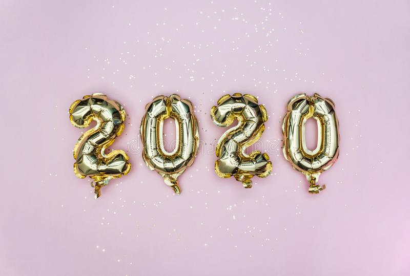 Happy New year 2020 celebration. Gold foil balloons numeral 2020 and golden stars on pastel pink background. Flat lay. stock photos