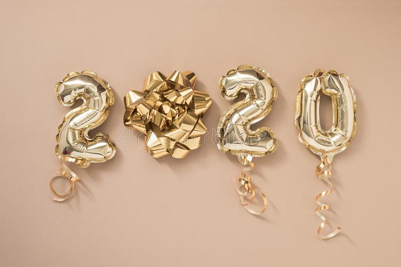 Happy New year 2020 celebration. Gold foil balloons numeral 2020 isolated on pastel beige background. Flat lay. Holiday christmas party decoration stock photography